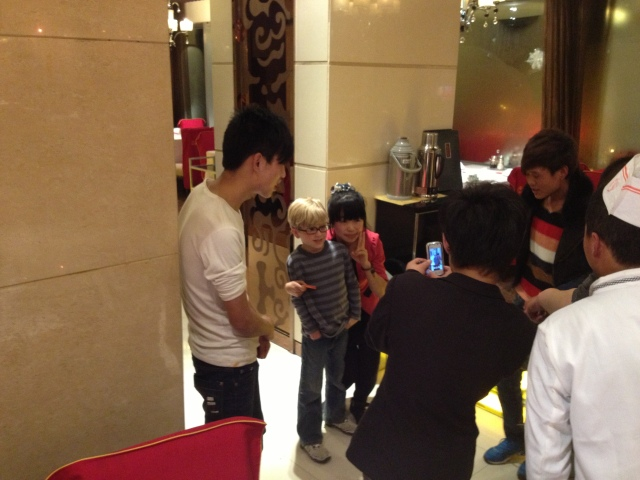 The waiters and waitresses at the hotpot restaurant surround Asher for the chance to get a picture of themselves with him on their phones :-)
