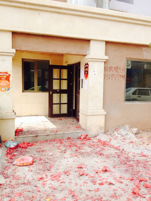 Debris right after a long red string of firecrackers went off outside our building entrance